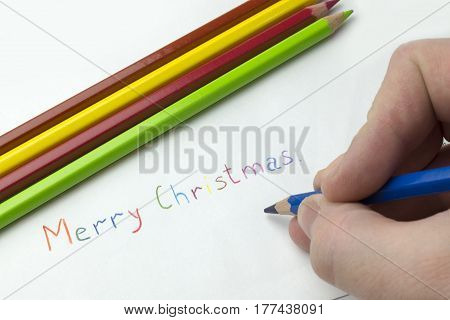 Hand wrote the words merry Christmas on a white background.