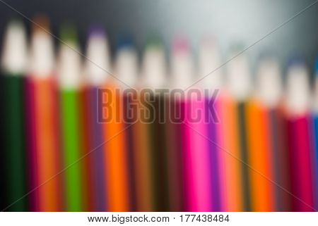 Colored Pencils Set On Black Wood Background In Disfocused,