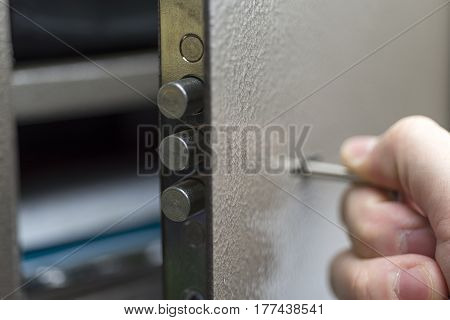 The hand with the keys opens the safe Deposit box protected.