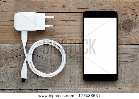 Smartphone and charger on old wooden table