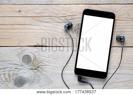 Smartphone and earphones on old wooden background