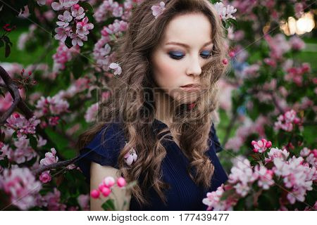 Clouse-up portrait of a young curly-haired girl with closed eyes in a blue dress standing among a blossoming apple-tree