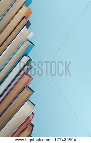 Book stacking. Open book hardback books on wooden table and blue background. Back to school. Copy space for text
