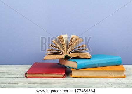 Open book hardback colorful books on wooden table. Back to school. Copy space for text