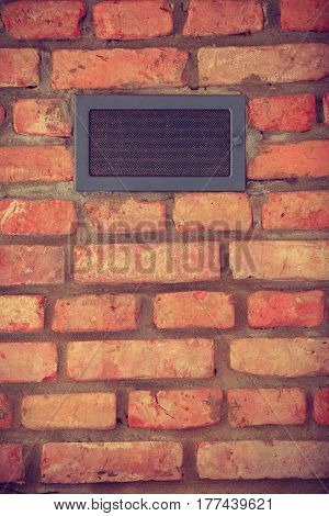 Textures and close up detailed patterns concept. Vent on red brick wall