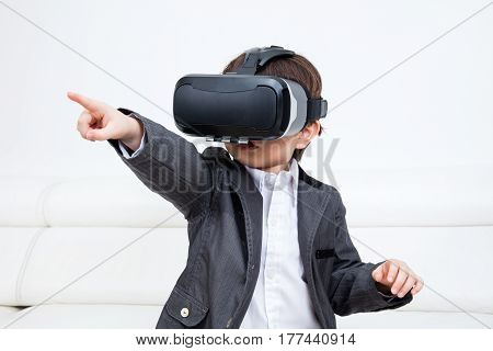 Asian Chinese Little Boy Wearing Virtual Reality Headset At Home