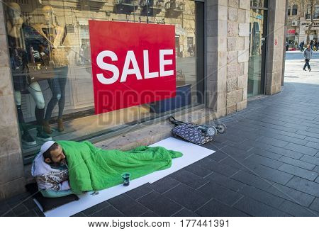JERUSALEM, ISRAEL - MARCH 06, 2017: The beggar homeless man is lying on the sidewalk near the shop window, on the window there is the inscription