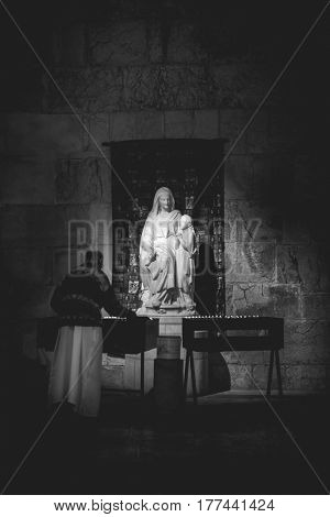 JERUSALEM, ISRAEL - MARCH 06, 2017: Statues of St. Anne and the young Virgin Mary with lighted candles at the foot of the sculpture in the Church of St. Anne in Old City of Jerusalem Israel