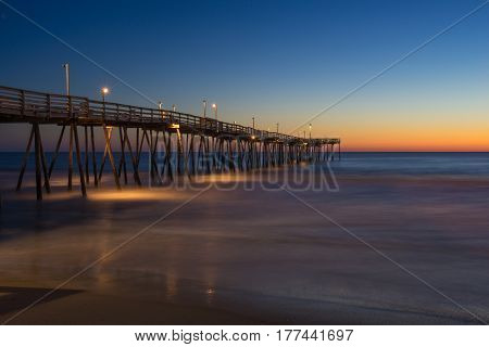 Sunrise long exposure of fishing pier along the beach of the Outer Banks of North Carolina