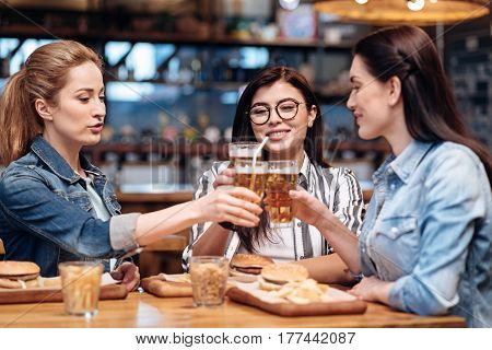 Favorite place. Beautiful women wearing casual clothes holding bocal of beer while saying toast