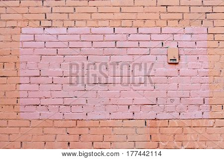 Yellow and brown brick wall with painted splotch as background or texture