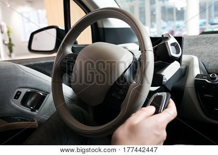 The man's hand with watch on the steering wheel