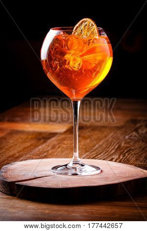 Spritz Aperol cocktail in a glass glass on a wooden board dark background