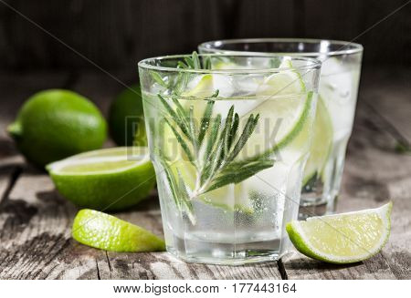 drink with fresh lime and rosemary on a wooden background