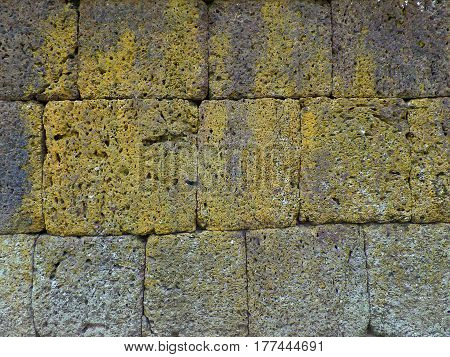 Closed up texture of rough ancient stone wall at Phanom Rung Historical Park, Thailand
