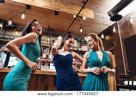 Dance time. Cute attractive friends wearing sexy dresses keeping smile on faces while moving their bodies