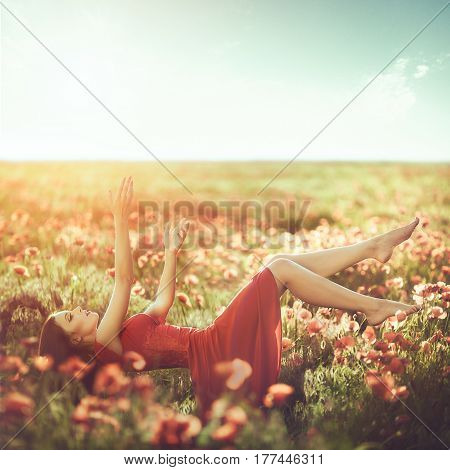 Woman flying above flower poppy field. Fantastic creative shot. Dreaming girl.