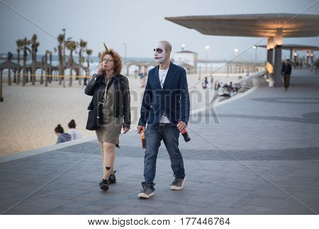 TEL AVIV, ISRAEL, MARCH 11, 2017: A young man and a girl in a carnival make-up and costumes are walking along the embankment.