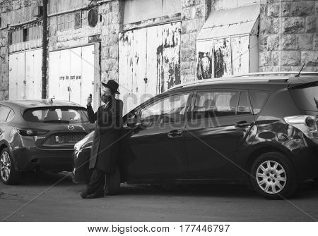 JERUSALEM, ISRAEL - MARCH 06, 2017: Orthodox quarter of the city. Hasid talks on his mobile phone