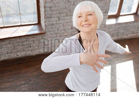 Full of joy. Elegant delighted aged woman performing in the ballroom while demonstrating grace and learning new dance step
