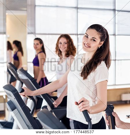 Group of happy young women running on treadmill in gym.