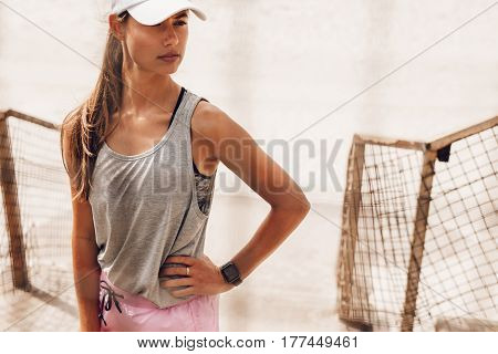 Portrait of beautiful and fit young woman standing outdoors and looking away. Female runner relaxing after running workout at beach.