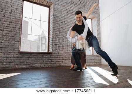 Enjoying active lifestyle together. Charismatic mature experienced dance teacher tangoing with senior woman while having training session and learning flexible step