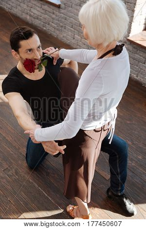 Full of expressiveness. Charismatic mature passionate dance couch tangoing with senior woman while having training session and holding rose in his mouth