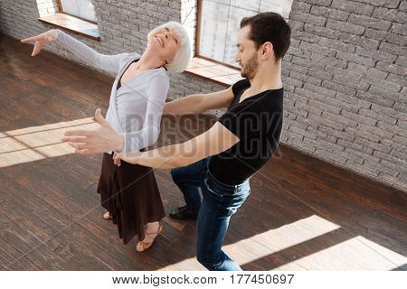 Enjoying every dance movement. Optimistic graceful passionate dance couple tangoing while having training session and expressing positive emotions