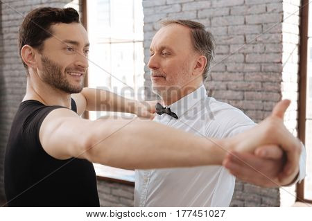 Taking part in the art performance. Cheerful helpful skilled dance teacher tangoing with senior man while having training session and teaching new dance step