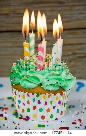 flaming candles in green frosting on cupcake with sprinkles
