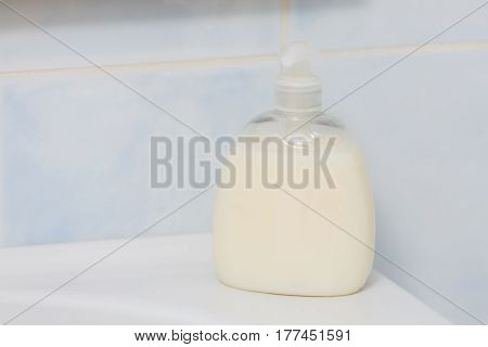 Bathroom hygiene objects concept. Liquid soap in plastic bottle with pump standing on sink.