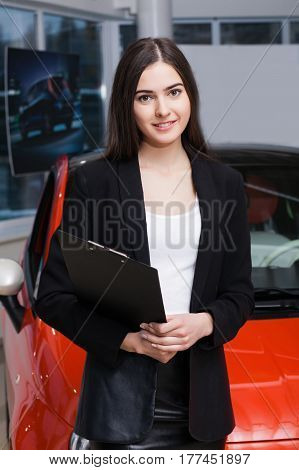 Beautiful female seller shows the car in the showroom