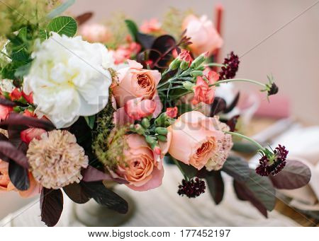 wedding flowers composition in peach, pink , purple and claret tones as background. Bouquet from fresh spring flowers. DOF.