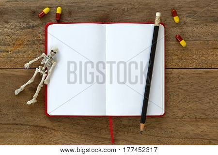 White skeleton dead body bones resting on blank white notebook with yellow red dangerous capsule on wooden background