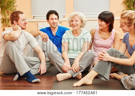 Group and senior woman in yoga class talking after class
