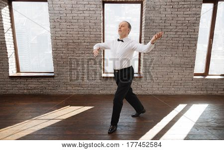 Full of grace. Charismatic positive inspired senior man performing in the ballroom while showing dance skills and rehearsing new dance step