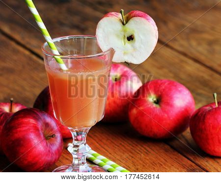 Fresh unfiltered organic apple juice on wooden table with apples
