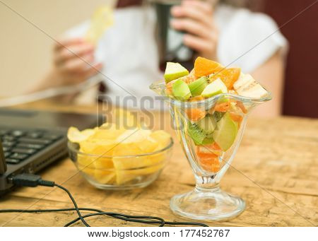 Tropical fruit salad and potato chips in front of a laptop. The child spends time at the computer.