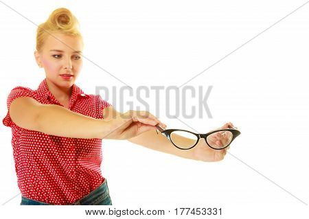 Ophthalmology sight problems stylish eyeglasses concept. Blonde pin up girl wearing red shirt holding black retro glasses. Studio shot isolated