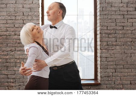 Full of happiness. Flexible delighted positive elderly couple dancing in the ballroom while improving dance skills and tangoing