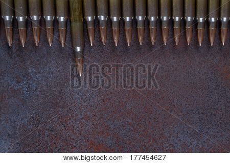 A row of ammunition. Concept of the first shot. On a rusted metal background