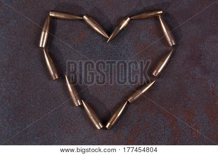 Heart symbol laid out on a dark background from bullets