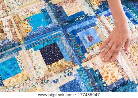 The caucasian female hand touching a color patchwork quilt with blue geometry pattern. Part of Colorful Scrappy blanket.