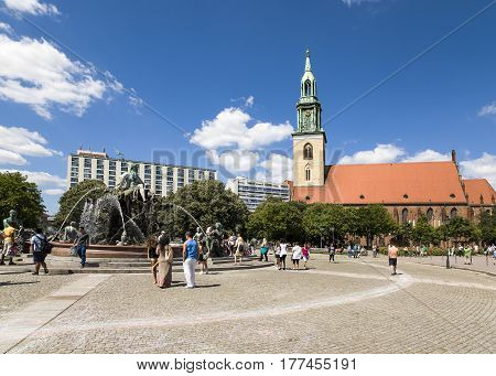 BERLIN GERMANY - 20 JUNE 2016: Neptune fountain and St. Mary's Church - Marienkirche near Alexanderplatz Berlin Germany 20 July 2016