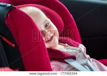 Little girl is seating in the car safety seat