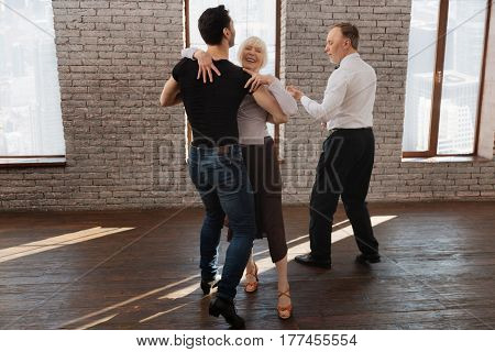 Enjoyable process of learning . Careful mature skilled dance couch teaching aged people while having training session and waltzing