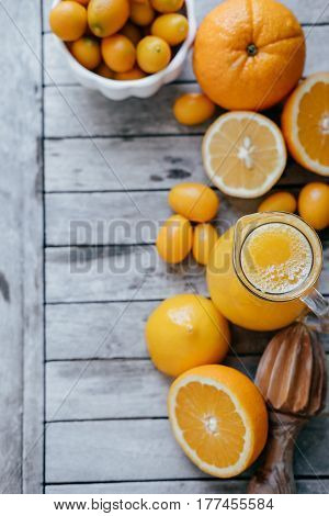 Vertical Photo With Kumquat In A White Bowl, Oranges, Lemons And Fresh Juice Squeezer On Wooden Boar