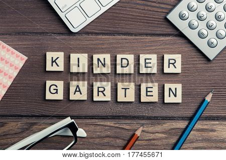 Wooden cubes on business workplace spelling Kinder Garden