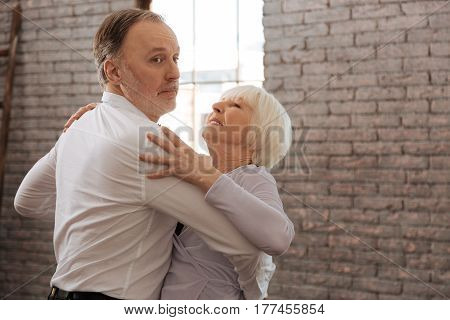 Feeling younger. Gifted concentrated positive senior dance couple waltzing in the dance studio while demonstrating dance skills and expressing peacefulness
